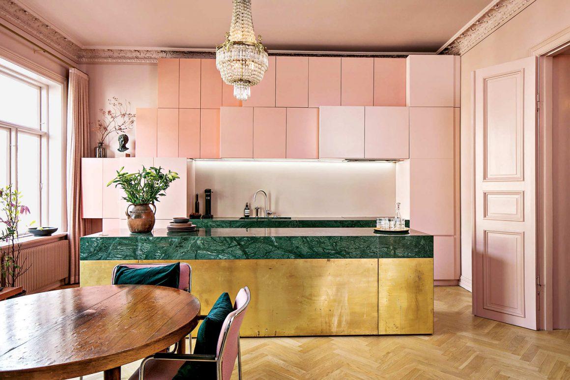 cozinha com bancada dourada e lacas rosa