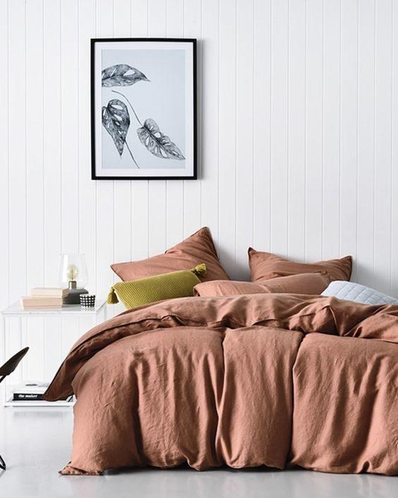 dormitório com roupa de cama em tom terroso alaranjado.
