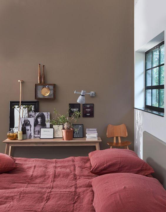 quarto em tons terrosos. parede esverdeada e roupa de cama alaranjada.