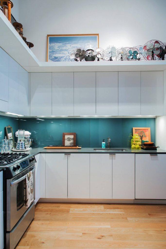 cozinha branco com espelho da bancada em vidro azul turquesa