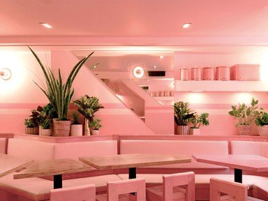 restaurante com paredes sofás e mesas rosa