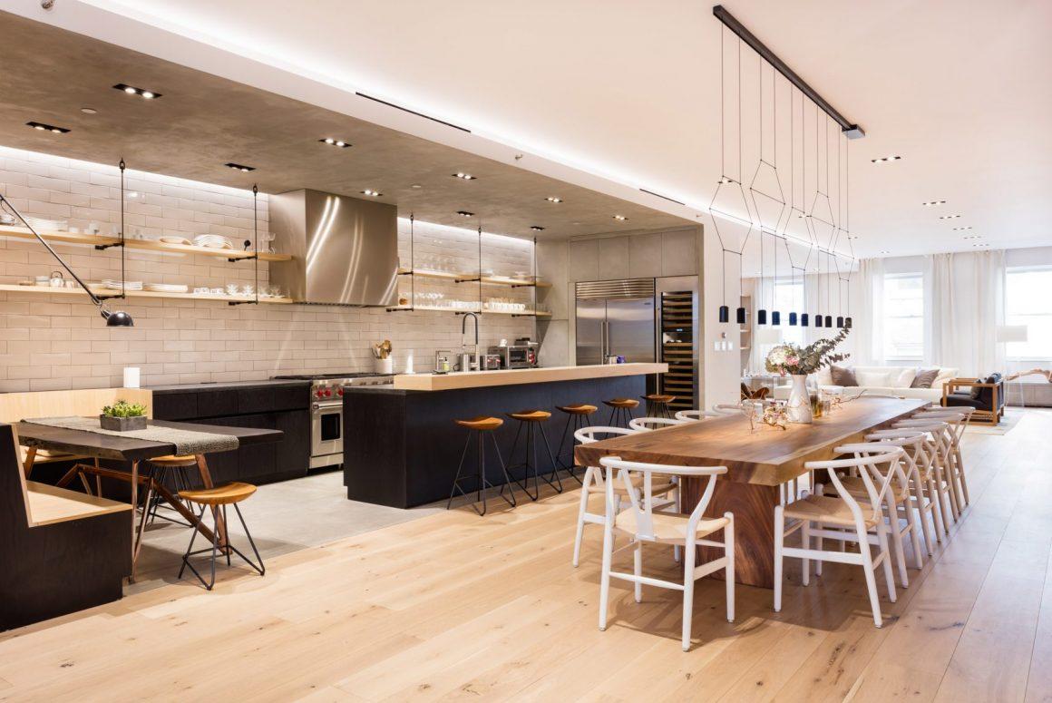 loft com piso de madeira clara, cozinha e sala de jangtar completamente integrada