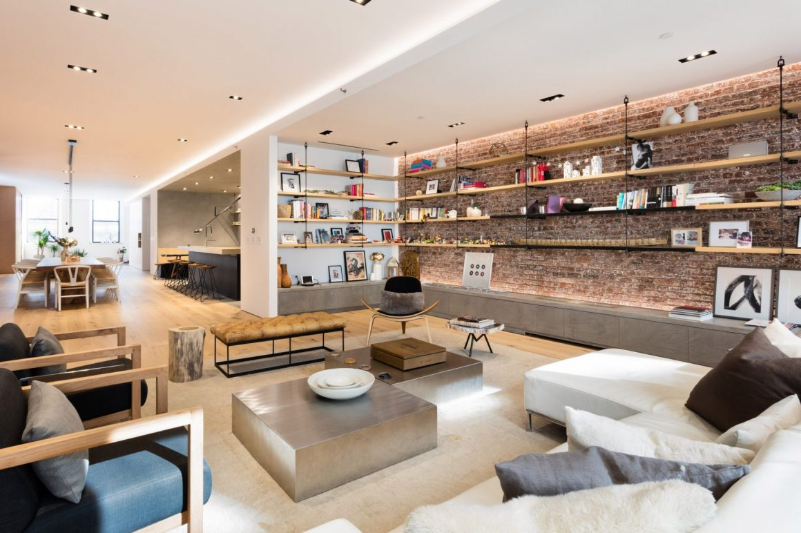 Living de loft com piso de madeira clara e estantes com prateleiras tirantadas