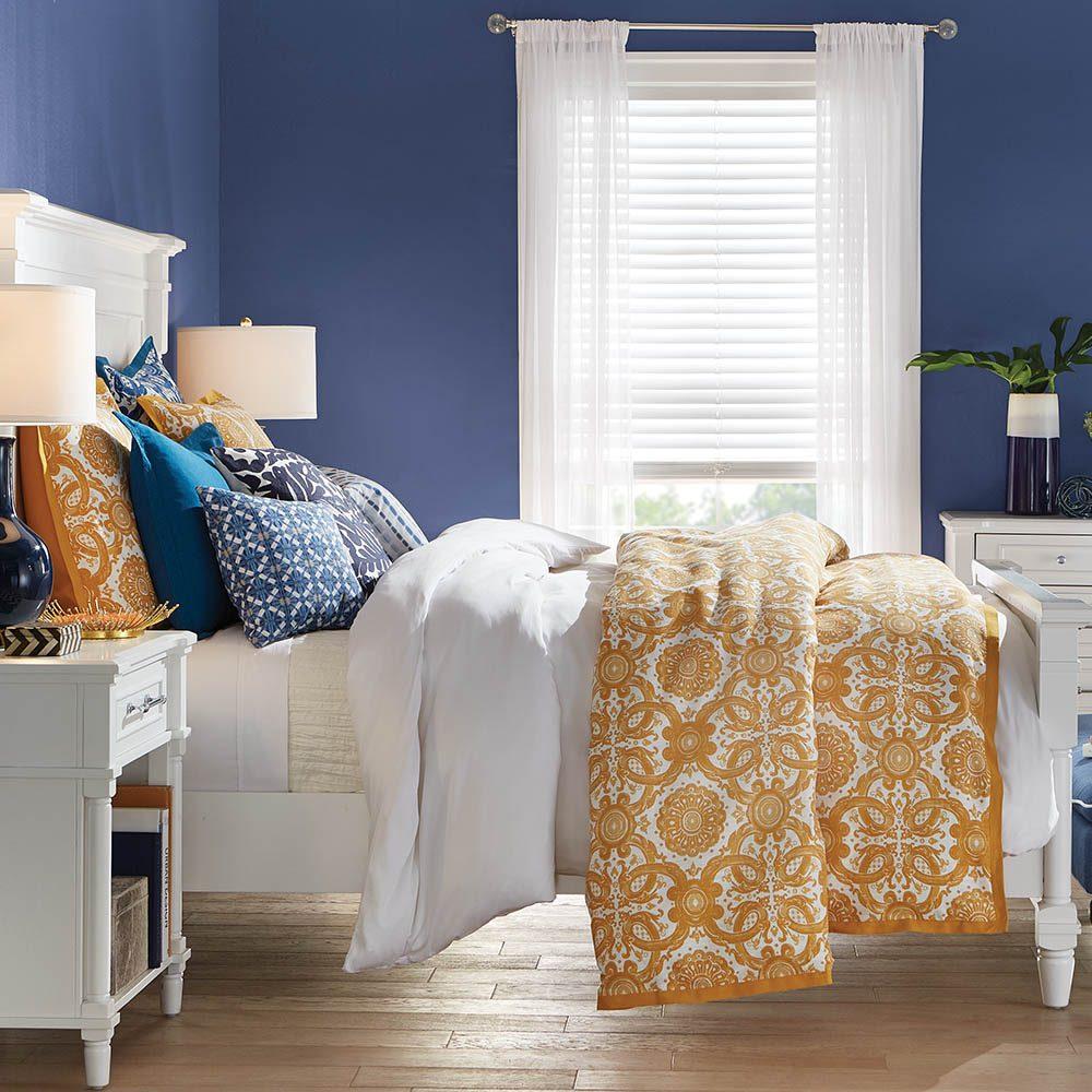 cama branca com almofadas azuis e amarelas