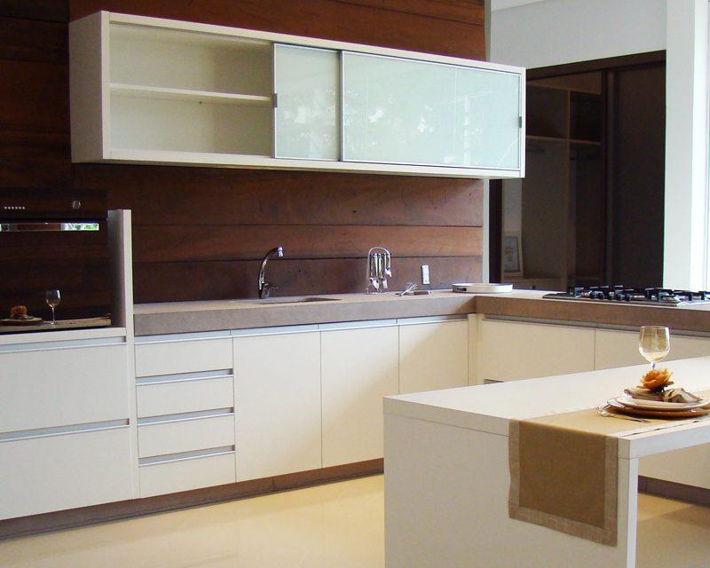 cozinha com painel de madeira escura e armario aereo em vidro