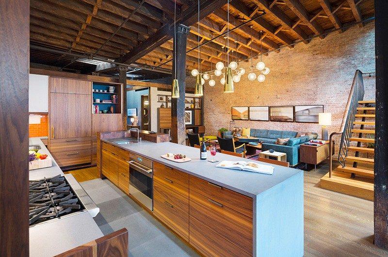 Living industrial com pé direito duplo, bancada da cozinha em pedra cinza, madeirame do forro aparente