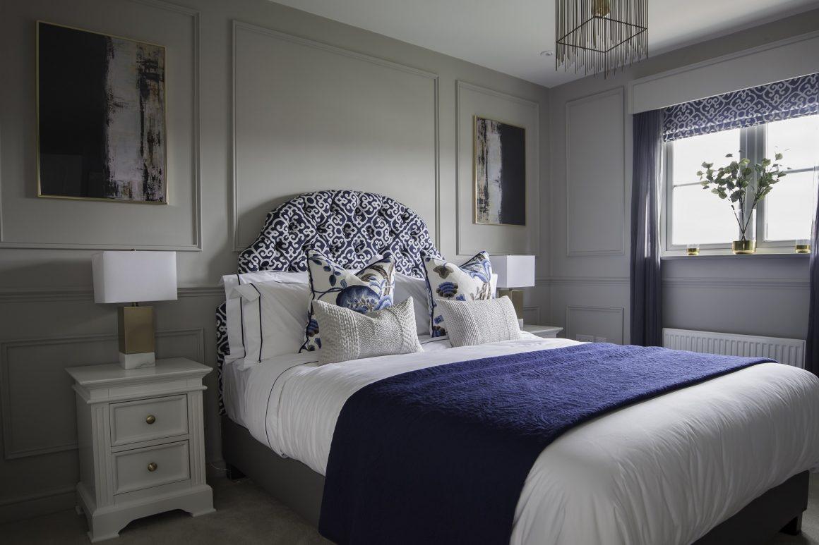 cama branca com almofadas estampadas e manta azul marinho
