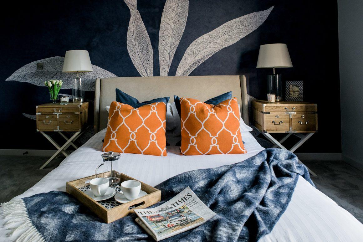 cama neutra com almofadas estampadas laranja