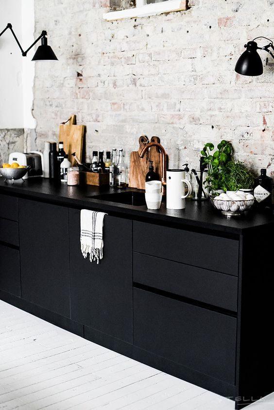 cozinha preta com décor industrial com parede branca de tijolinho.