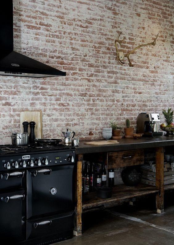 cozinha preta de mood industrial com parede de tijolo