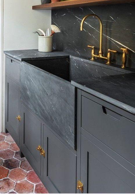 cozinha preta com puxadores e torneira dourada