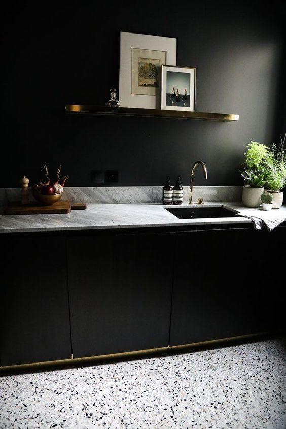 cozinha preta com toque de dourado e bancada em mármore.