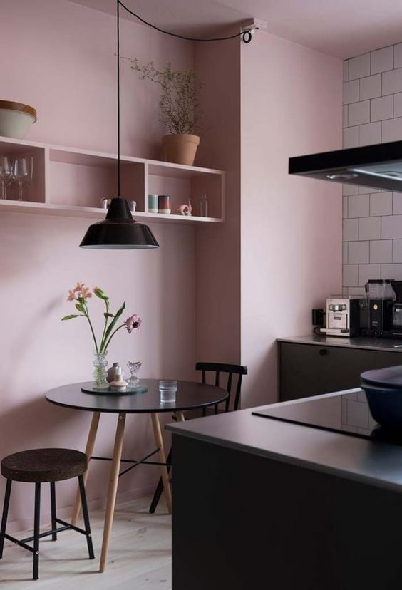 cozinha preta com parede pintada de rosa