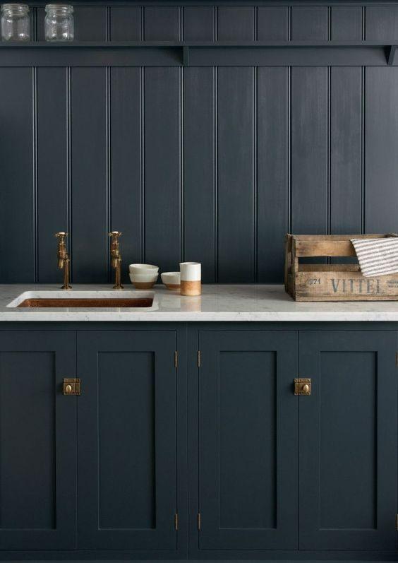 cozinha preta com bancada branca e metais dourados