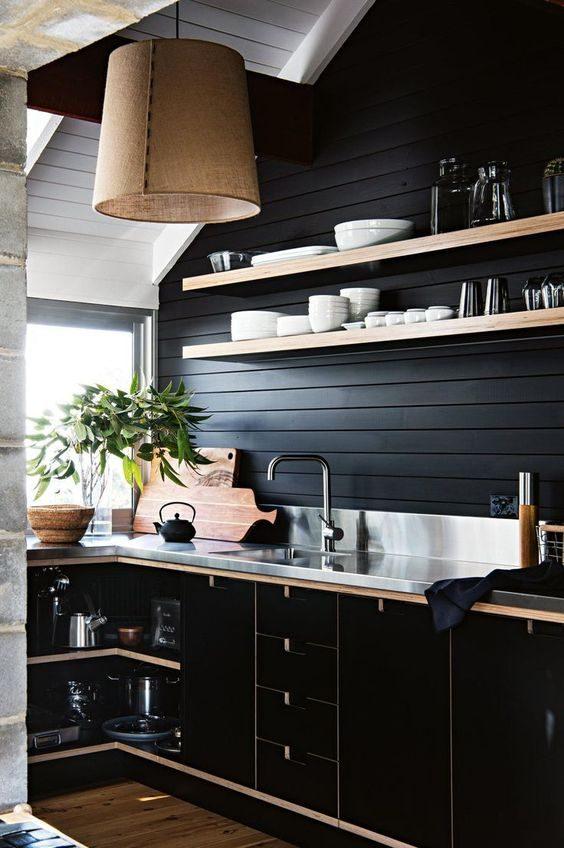 cozinha preta com objetos rústicos em palha