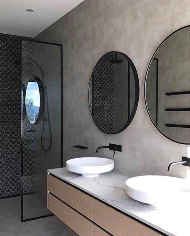 banheiro minimalista com concreto aparente e espelhos redondos