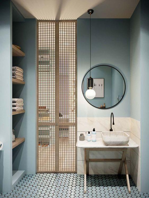 banheiro azul claro com espelho redondo