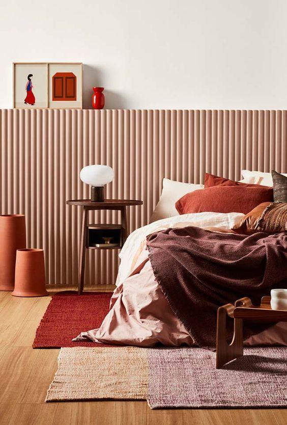 cama arrumada com lençóis em tons terrosos.