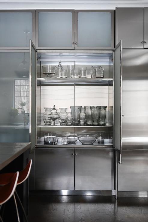 cozinha com bancada metalica e armarios com porta de vidro