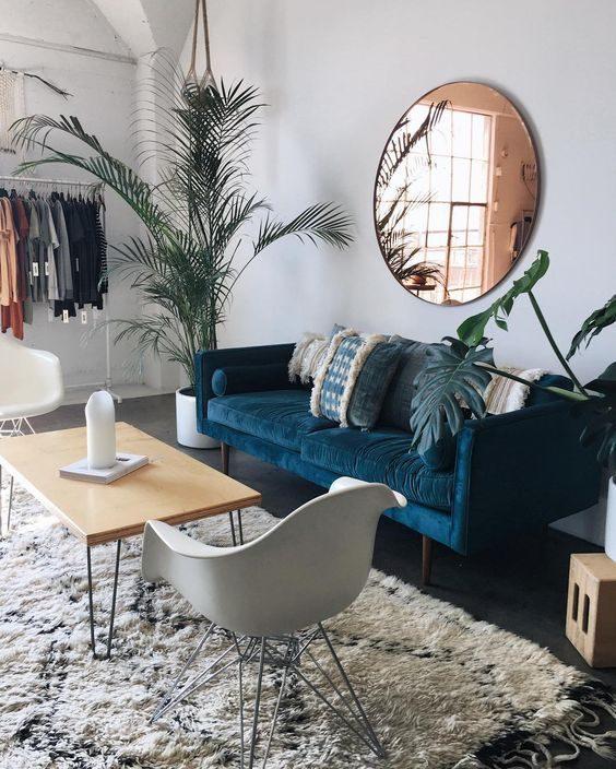 espelho redondo na sala em cima do sofa azul