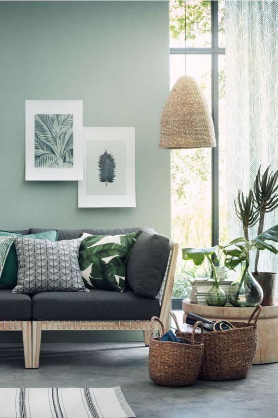 sala de estar com parede em verde neo-mint e objetos em palha artesanais.