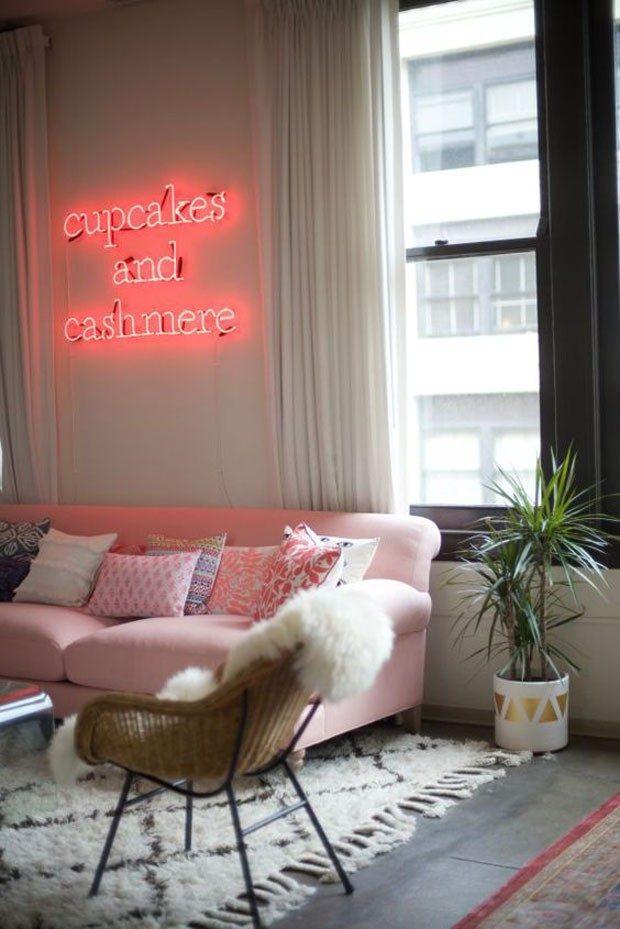 Estar girlie com sofá e luminária neon rosa.