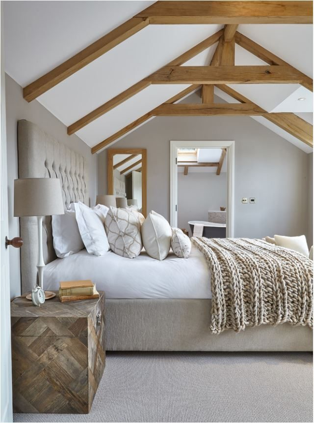 cama com lençóis brancos e manta de tricot por cima