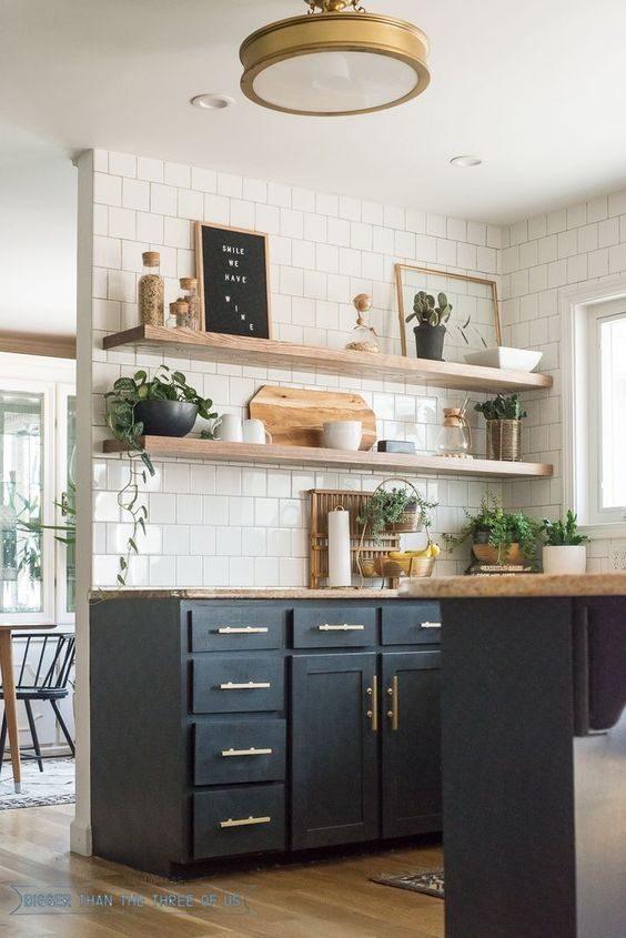 cozinha preta com subway tiles e decoração dourada