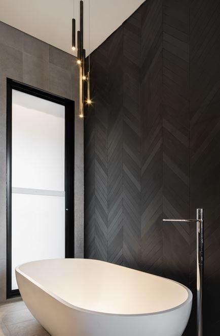 banheiro com parede em preto com textura de madeira em espinha de peixe