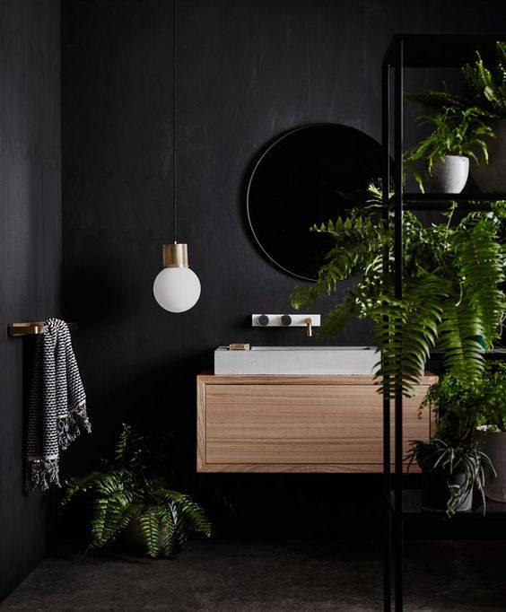 banheiro com decoração em preto e vegetação.