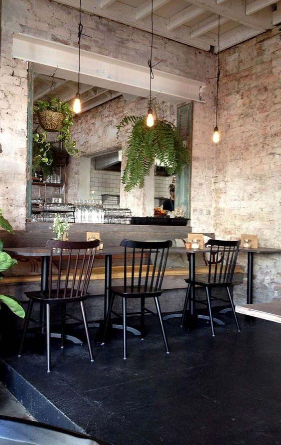 restaurante de estilo industrial com decoração de samambaias