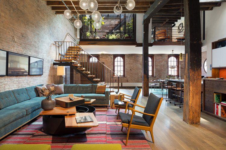 Living industrial com parede de tijolo aparente, pé direito duplo e cores no mobiliário