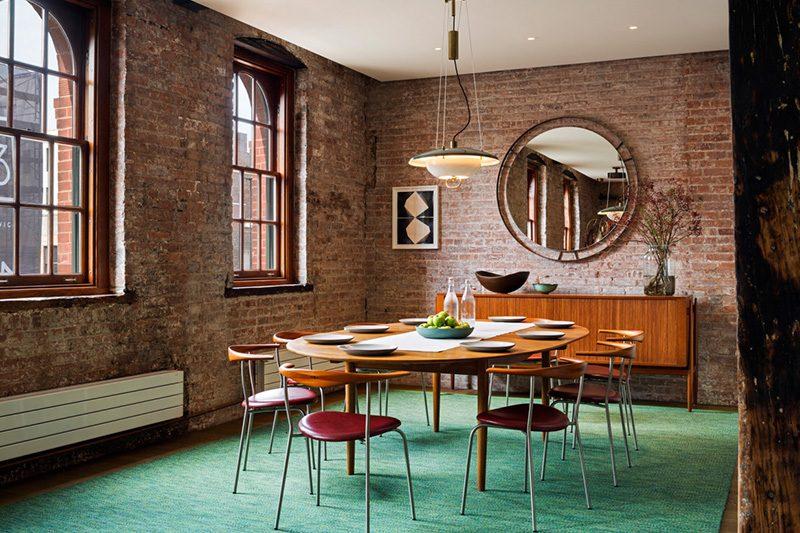 sala de jantar industrial com parede em tijolo aparente, tapete verde, mesa e cadeiras em madeira