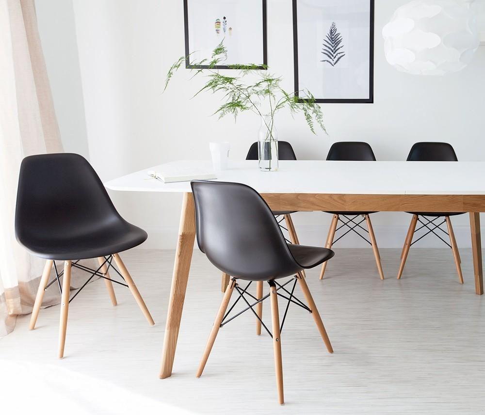 mesa de jantar com cadeiras eames pretas com pés de madeira