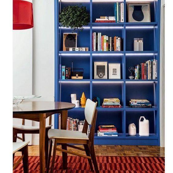 estante azul de nichos com livros
