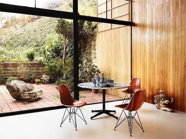 Sala de jantar com mesa redonda e eames de madeira com pés metalicos