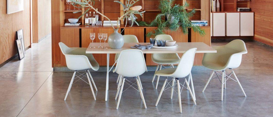 sala de jantar com piso cinza, mesa clara e cadeiras eames com braço estofadas